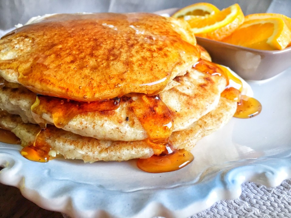 fluffy whole wheat vegan pancakes shown on a white plate with syrup dripping down the sides