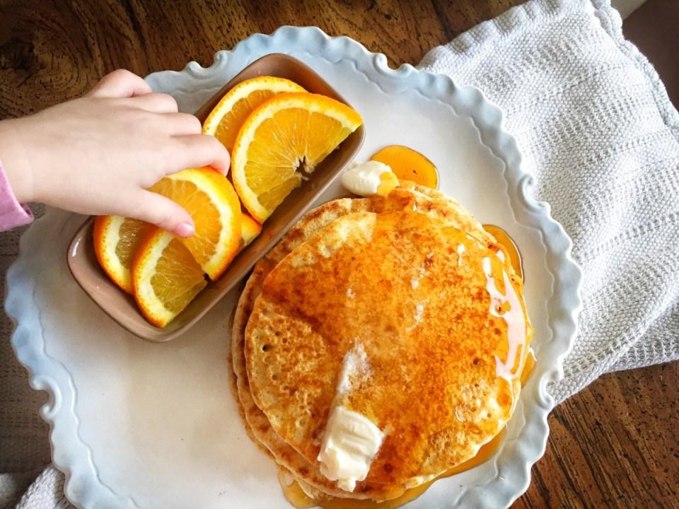 child reaching for oranges beside the fluffy vegan pancakes