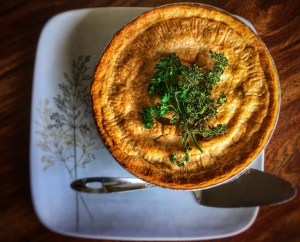 Image of a whole golden Vegan Chickpea Pot Pie with green herbs on top. There is a silver pie lifter pictured below the pie.