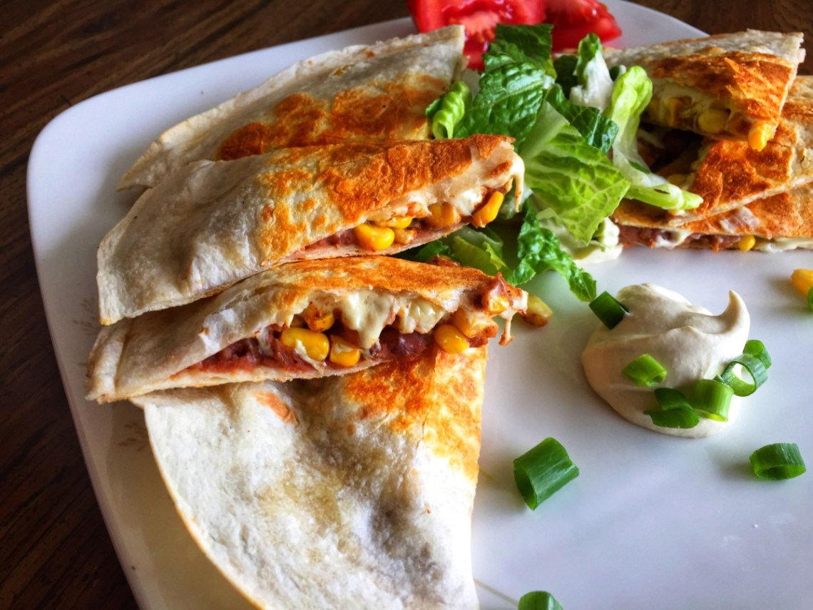 a side view of the easy re-fried bean quesadillas, plated and topped with cashew sour cream, chopped onion and diced tomatoes