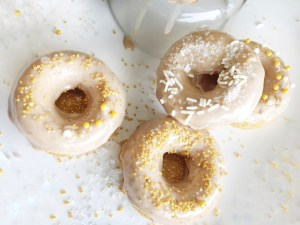 Vegan Pumpkin Spice Doughnuts! Image shows doughnuts stacked on top of each other with golden sprinkles