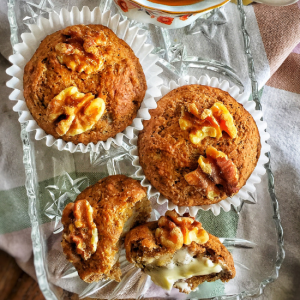 Vegan banana nut muffins shown with two muffins on the top of the plate, and another muffin split open with vegan butter