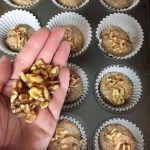 walnuts being placed on top of the raw spooned out banana nut muffins