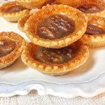 Image shows butter tarts stacked and plated on a white plate with a white background