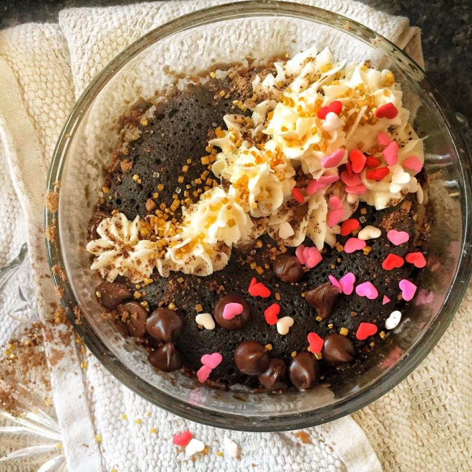 Vegan Chocolate Espresso mug cake shown in a glass bowl, topped with whipped cream and gold sprinkles