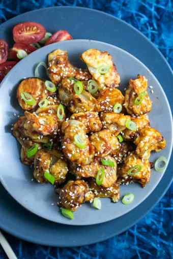 vegan sticky sesame cauliflower shown plated with green onions on top and a side of fresh tomato
