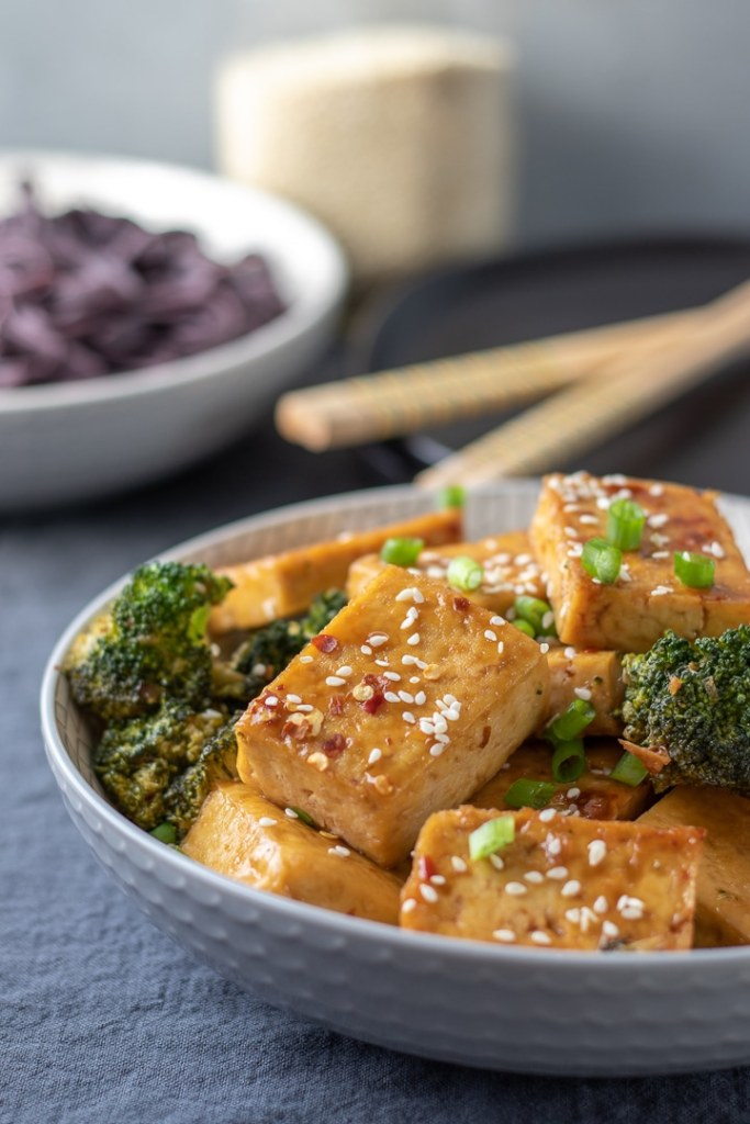 Sticky Sesame Tofu in a white bowl with chopsticks, sprinkled with scallions.