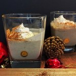 Vegan eggnog cocktail served in two glasses topped with whipped cream and cinnamon