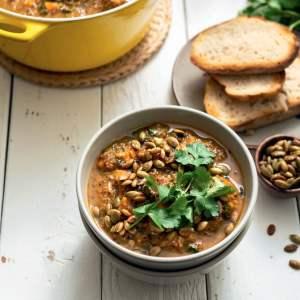 Smokey Sweet Potato soup in a white bowl topped with fresh cilantro leaves.