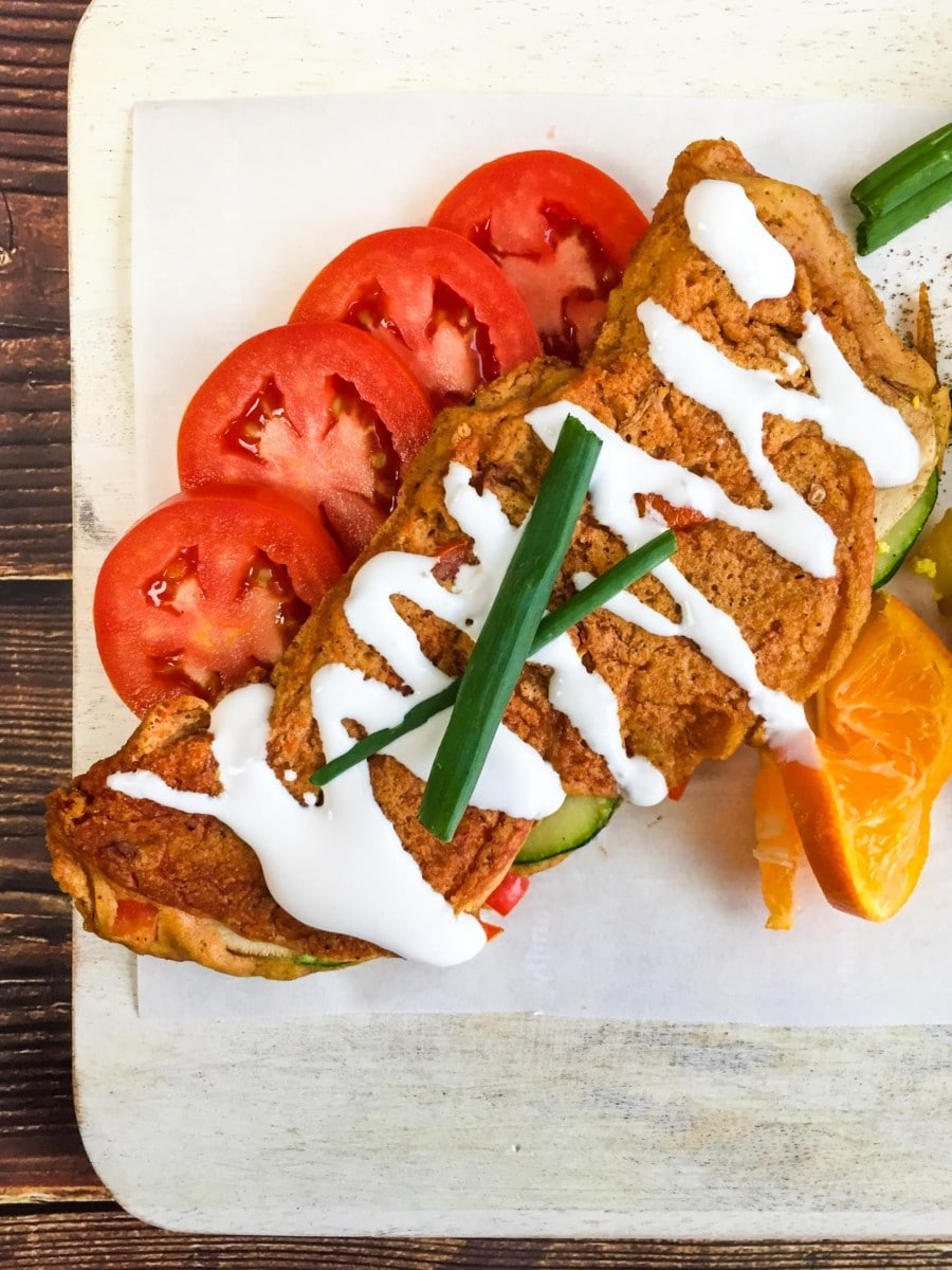 Vegan chickpea omelette on a white plate with sliced tomatoes and cashew cream drizzled on top.