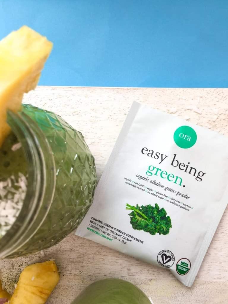 ora organic green smoothie powder shown on a white cutting board next to a pina colada creamy green smoothie