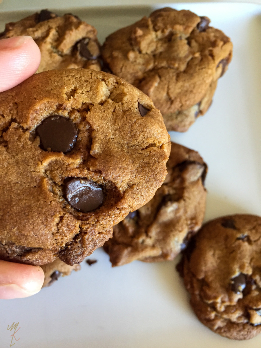 a crispy vegan chocolate chip cookie being held up to the camera