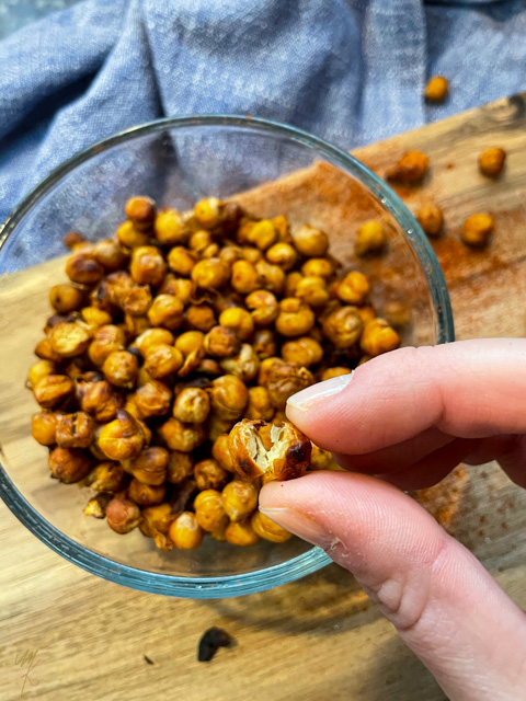 One crispy chickpea cracked open being held to the camera with a bowl of chickpeas below