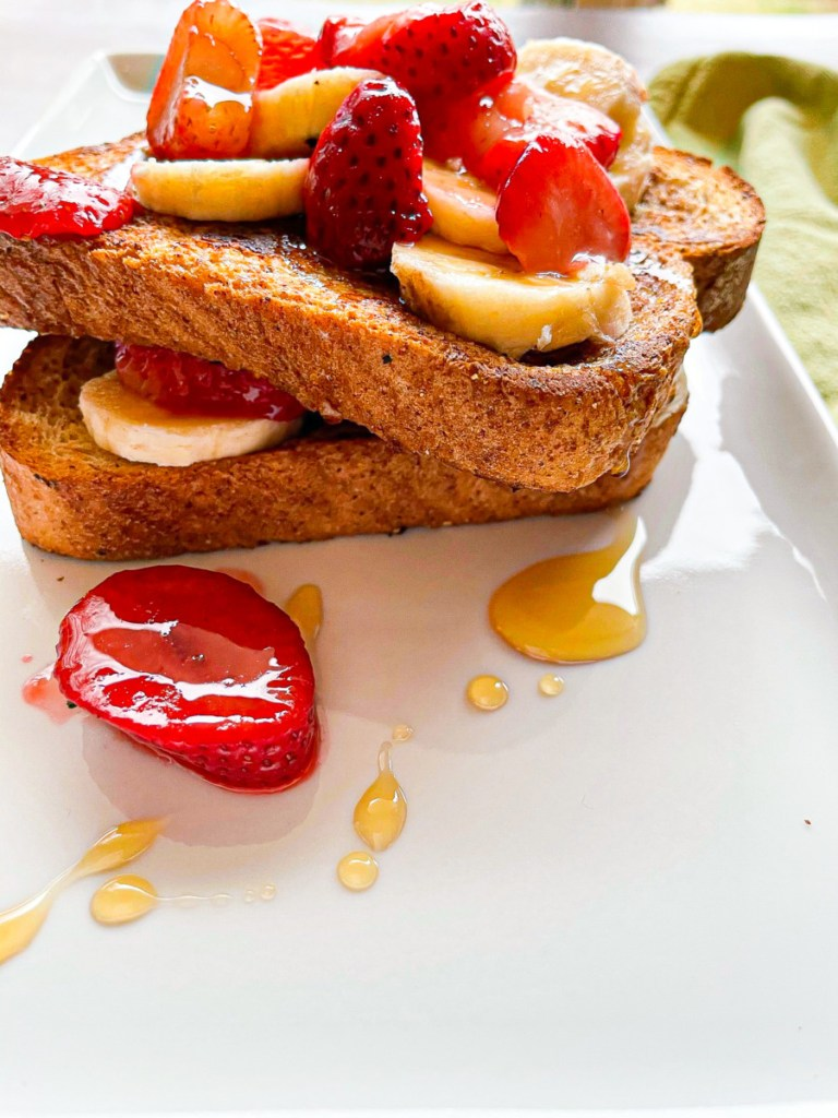 Vegan french toast topped with strawberries and banana on a white plate