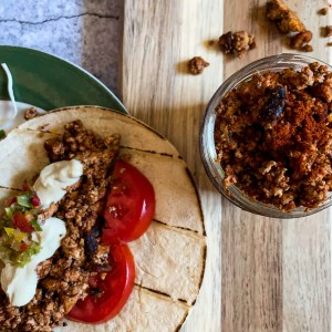Tofu Taco Meat in a corn flour tortilla with tomato and cashew sour cream