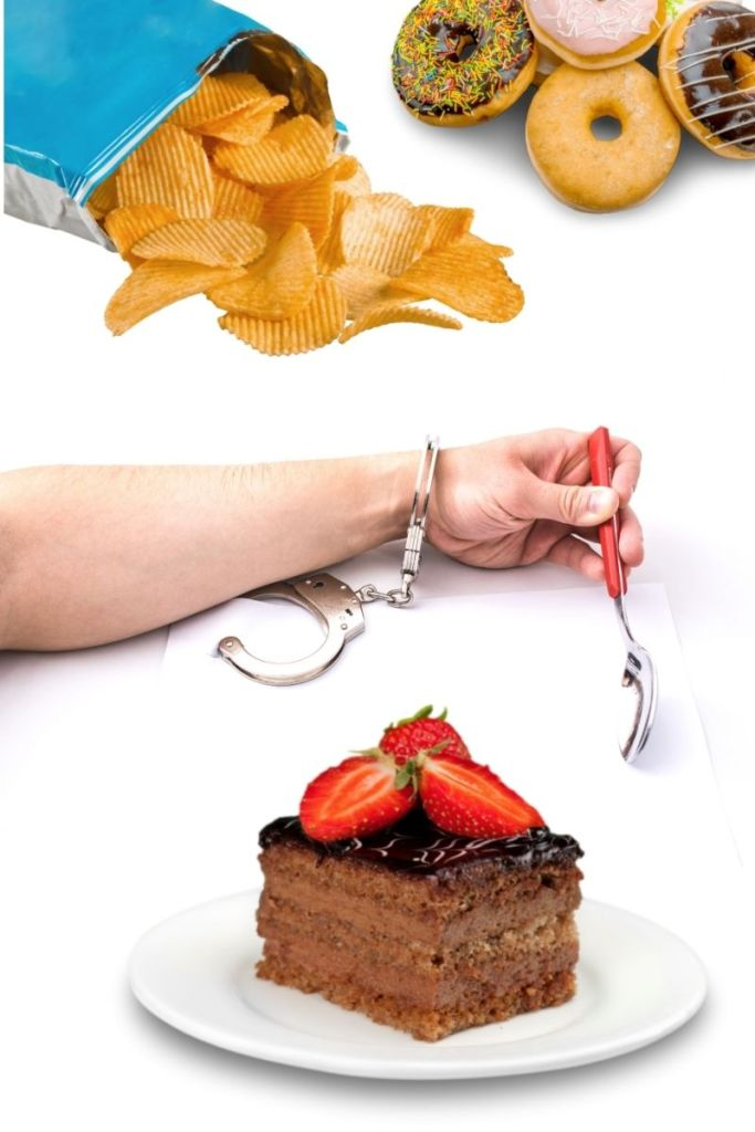 a womans hand is handcuffed to her fork over a plate of cake showing why shes not losing weight as a vegan due to toxic hunger and cravings