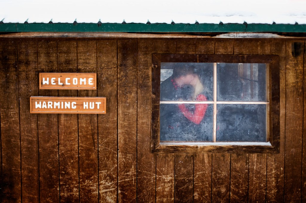 Romantic image of a couple kissing in a winter warming hut in Wyoming.