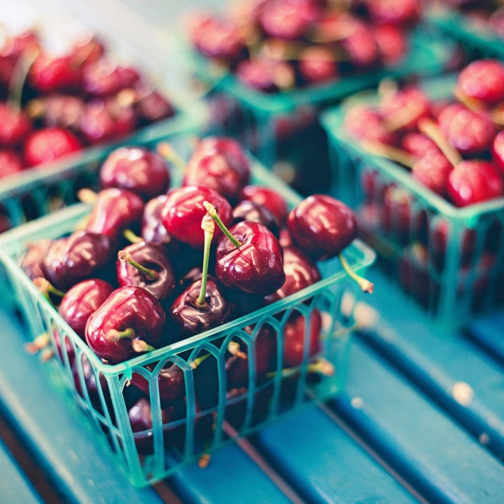 Cherries on a blue shelf in a farmers market in waterloo, CA.