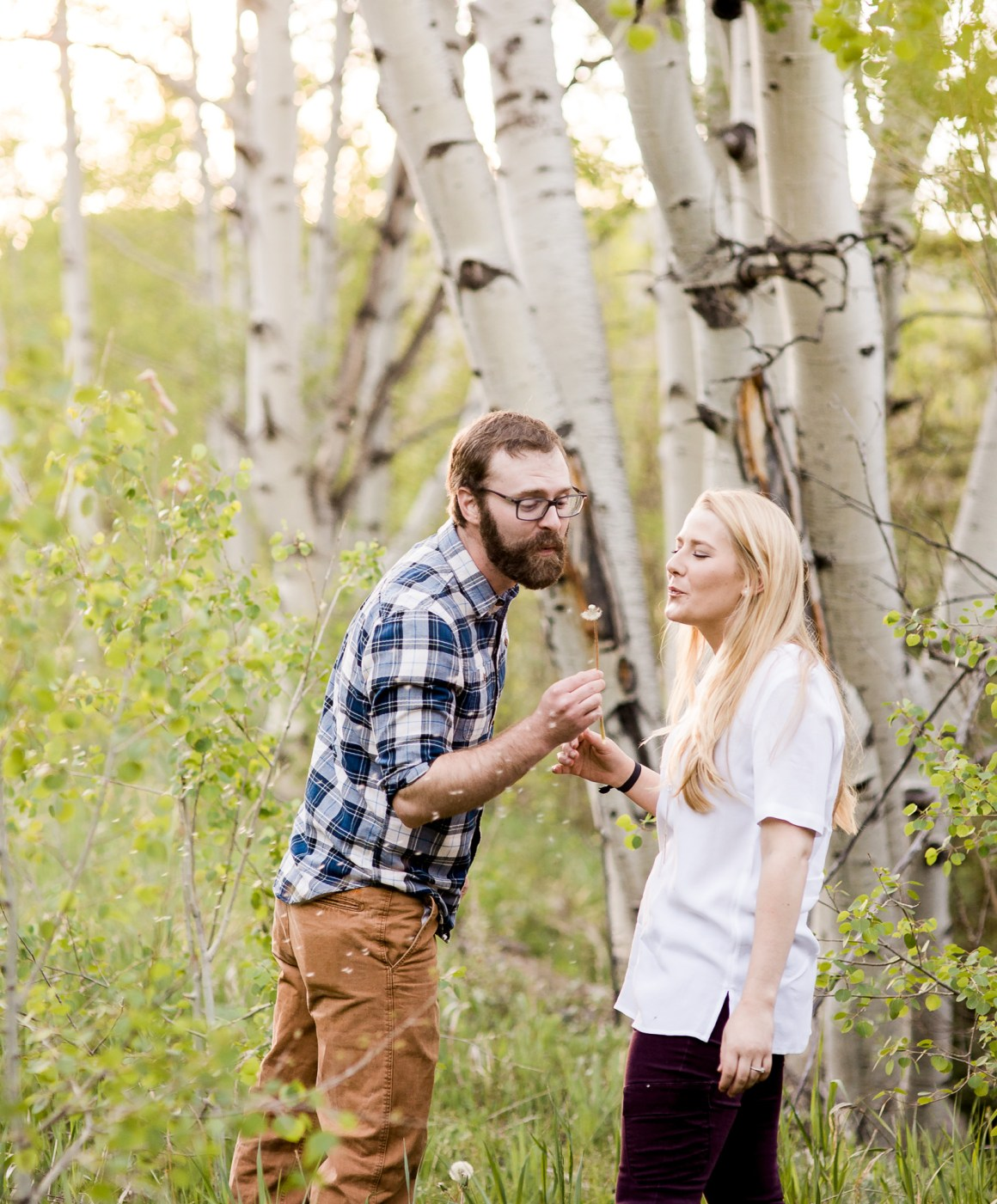Engagement photography in the mountains of Wyoming by Laramie based photographer. Couple blowing dandelion