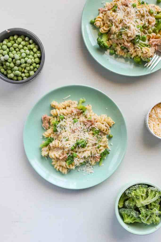 Creamy Homemade Tuna Helper on a green place topped with peas, broccoli and cheese. surrounded by bowls of peas, broccoli and cheese