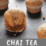 Chai tea muffins, one with a bit taken out of it, on a black surface
