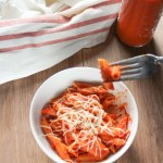 Bowl of red pepper penne on a wooden table with a jar of sauce and a napkin next to it.