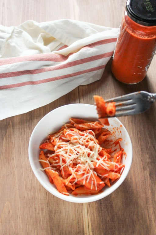 Red Pepper Penne win a bowl with a jar of sauce and a napkin next to it.