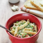 Prosciutto & Pea Alfredo with Penne in a red bowl. Bread and peas are behind it.