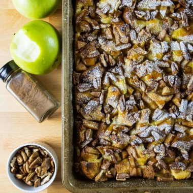 Baked Apple French Toast surrounded by apples, pecans, and a jar of cinnamon