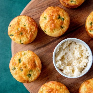 Jiffy Jalapeno Cornbread Muffins on a wooden board with honey butter