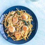 Scallops and Linguine with Lemon Caper Sauce on a blue plate next to parm cheese and water with a lemon