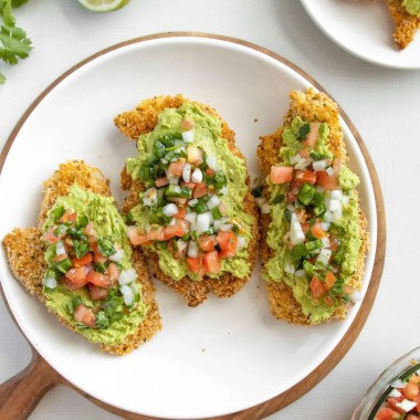 Crispy topped with Pico de Gallo Chicken and smashed avocado. surrounded by limes and cilantro