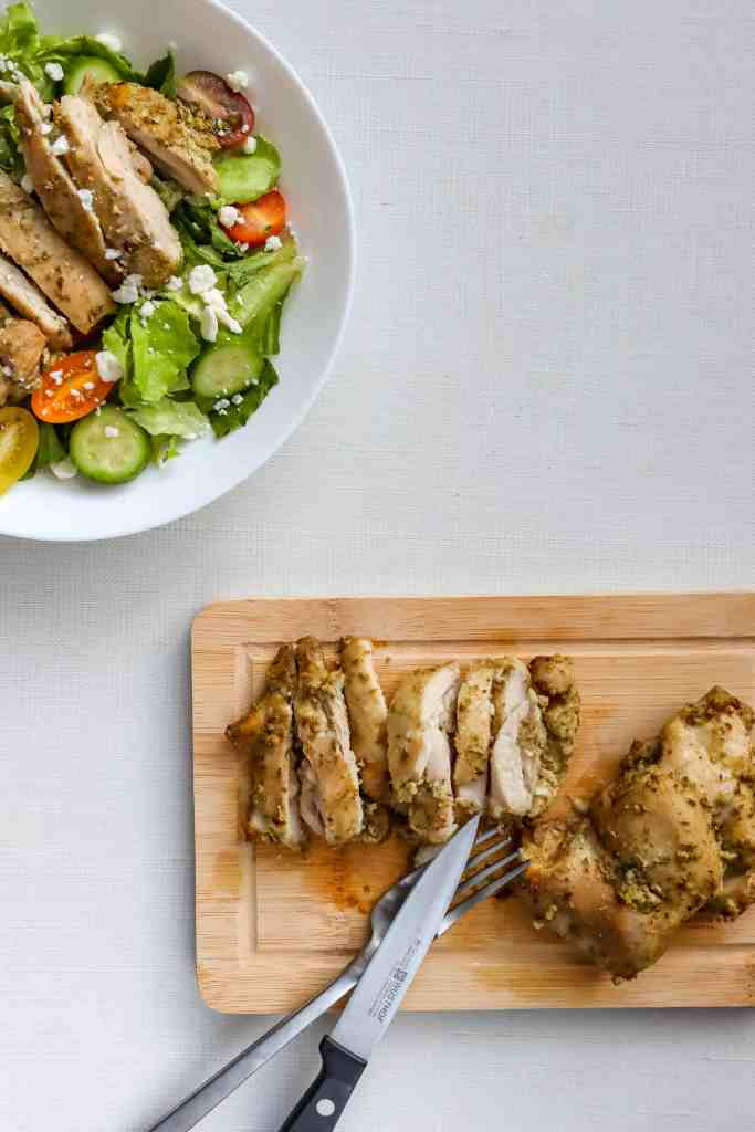 Greek Marinated Chicken Thighs  in a bowl with salad