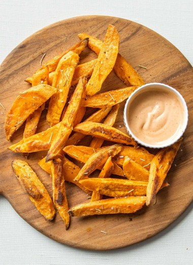 Baked Sweet Potato Wedges on a wooden serving plate with dipping sauce.