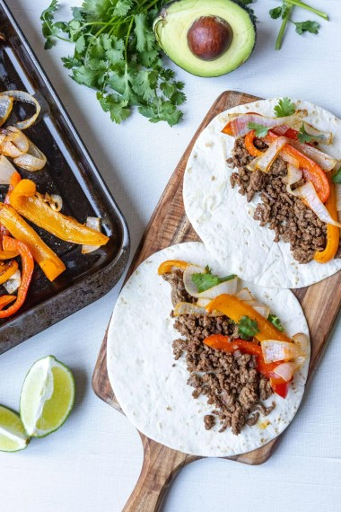 Ground Beef Tacos with Vegetables on a wooden serving tray.