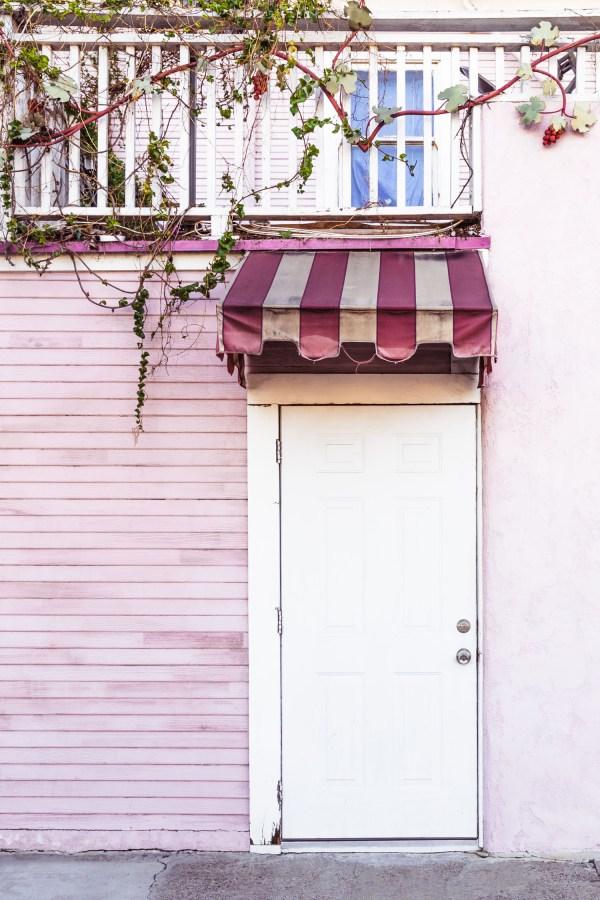A white door surrounded by pink wooden panels, pink stucco, and a pink striped awning