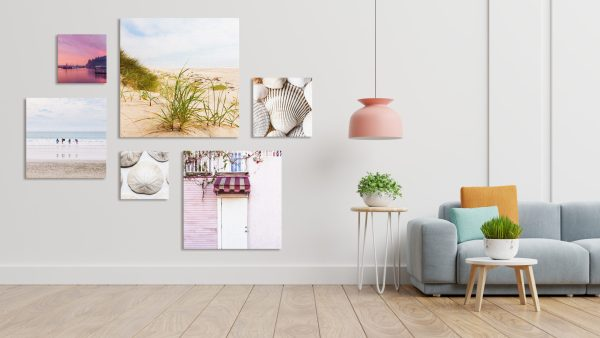 A grouping of six canvas print on an empty living room wall.