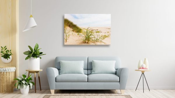 Canvas print of beach grass hung hover a couch in a living room.