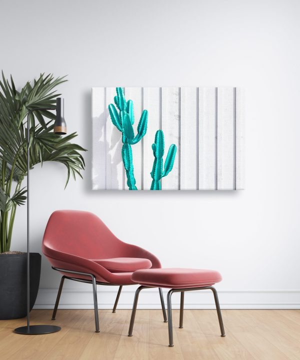 Canvas print of a teal cactus hanging on a wall over a couch.
