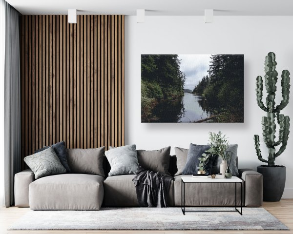 A canvas print of a lake and forest landscape hanging on a wall over a couch.