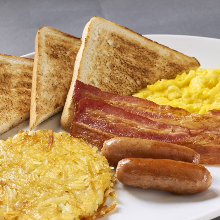 Here comes the big breakfast! What a beautiful sight of scrambled eggs with cheddar cheese, bacon strips, sausages, toasts, and hash browns together in one plate! Dig in!