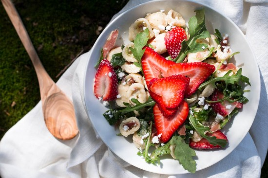 Overhead shot of orecchiette pasta salad with arugula, feta, and strawberries in a shallow white bowl next to a wooden spoon.