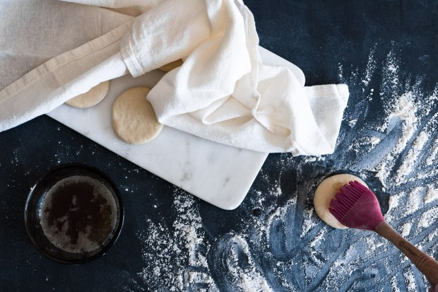 A cut circle of dough being brushed with brown butter on a floured surface next to other dough circles on a marble board partially covered with cloth.