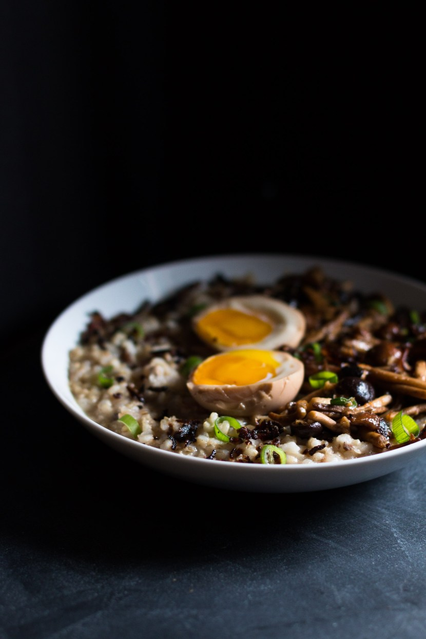 Vertical side shot of brown rice congee, stir fried mushrooms, and two ramen egg halves.