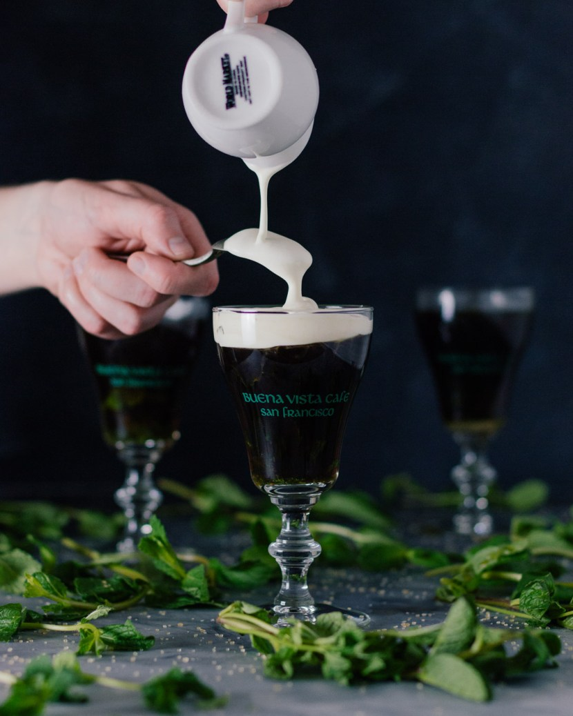Vertical shot showing a hand pouring cream into an Irish Coffee glass.