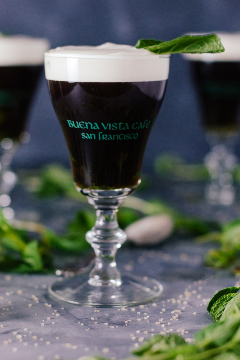 Vertical shot of an Irish Coffee topped with cream in a small glass goblet surrounded my mint leaves, grains of sugar, and other Irish Coffees.