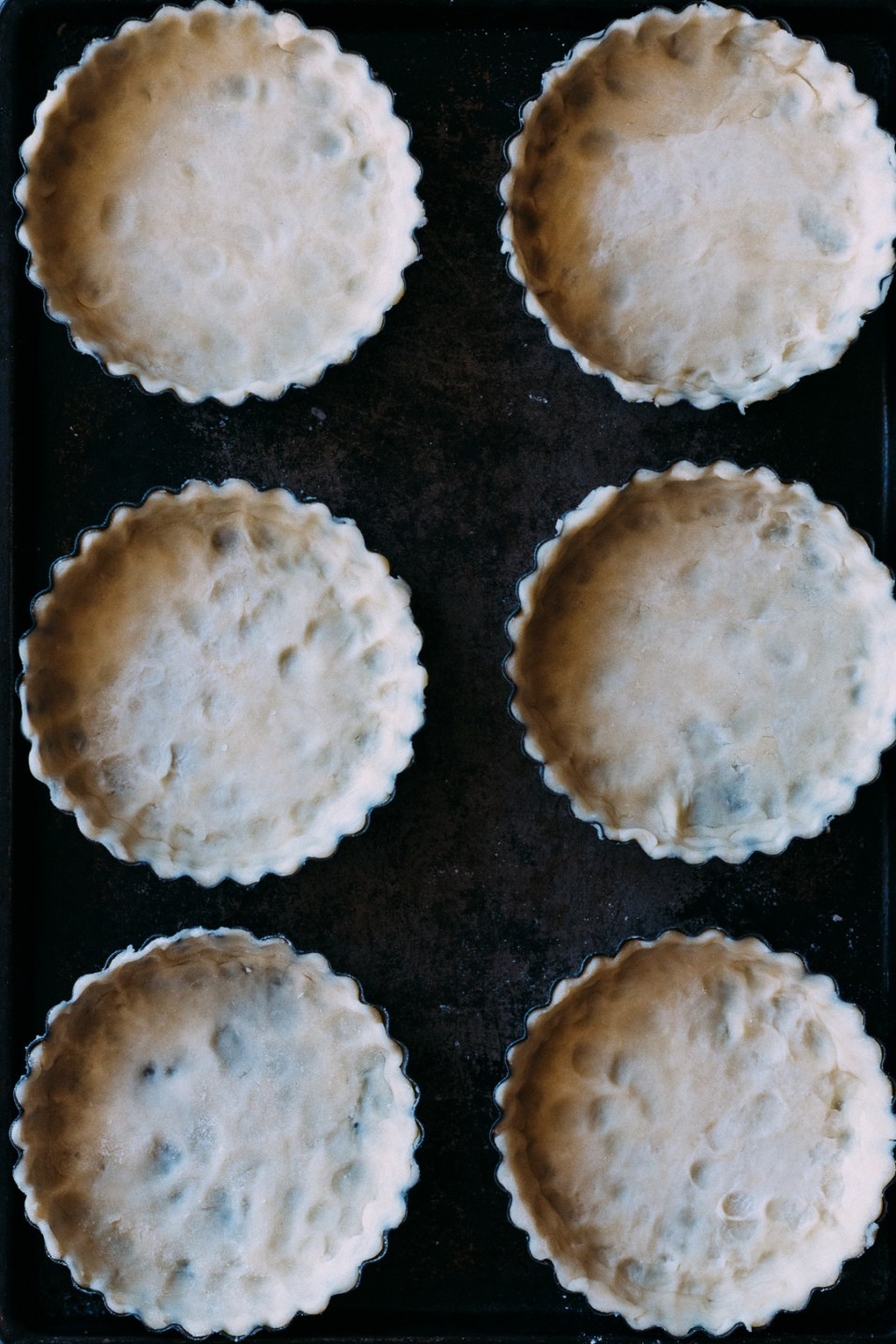 Overhead shot of 6 tart pans with uncooked crust in them.
