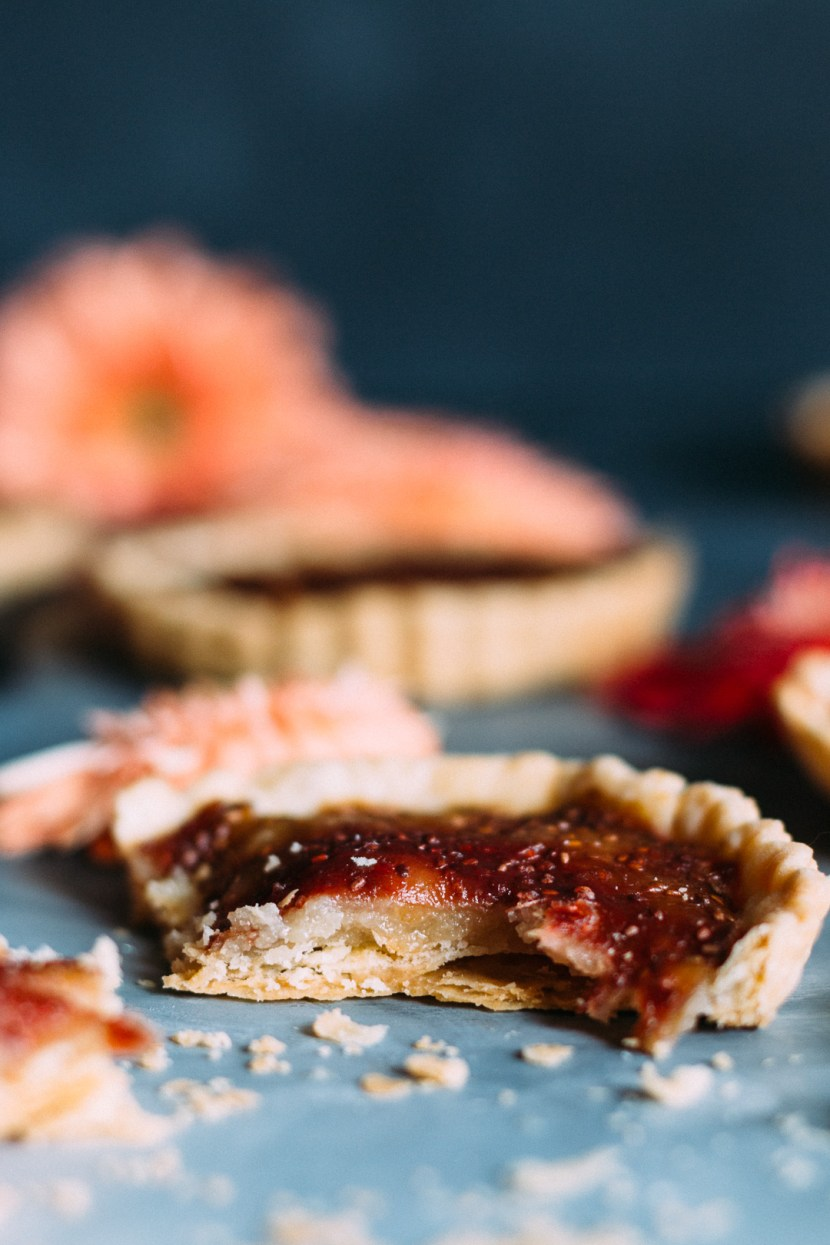 Vertical side shot of a rhubarb tart showing the crust, marzipan, and rhubarb jam layers.