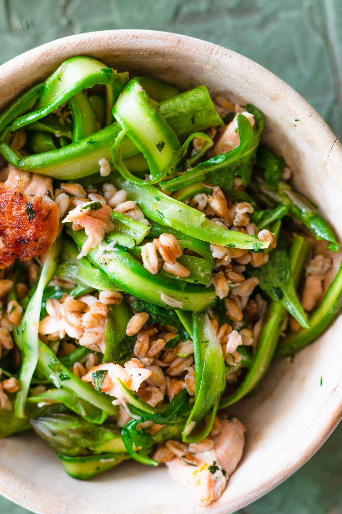 Close up overhead shot of a Salmon Grain Bowl filled with farro, asparagus, and salmon.