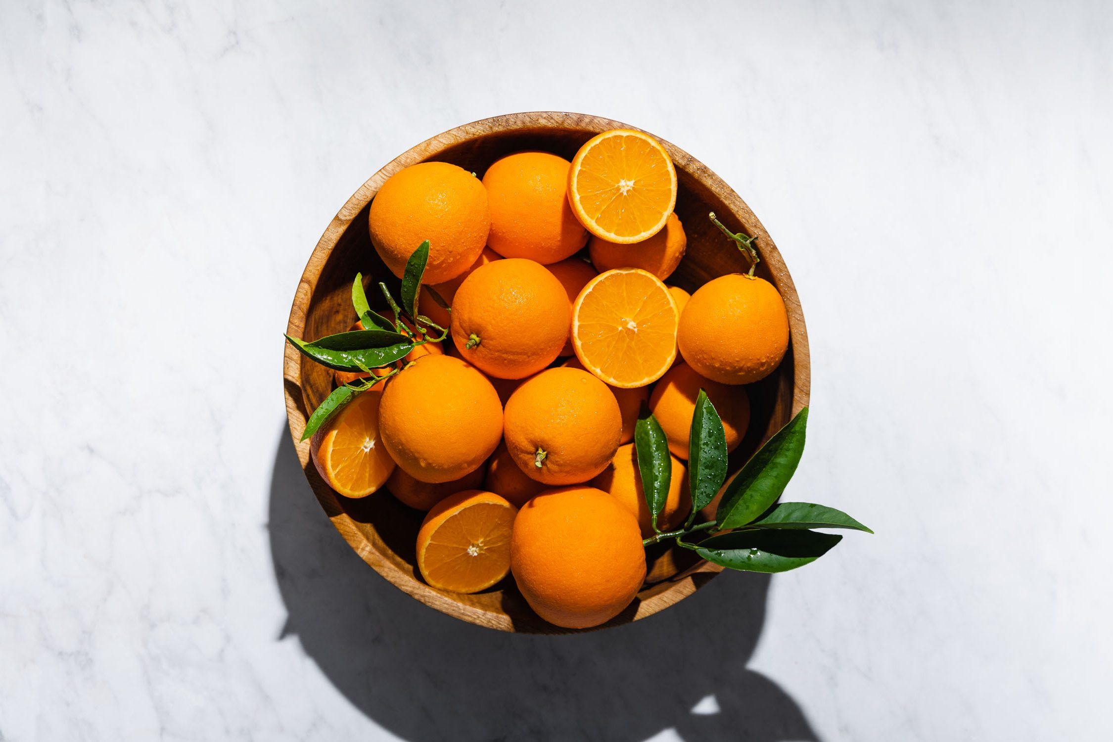 Overhead shot of a large wooden bowl filled with oranges.